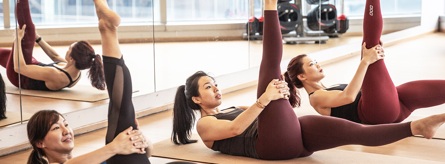 woman in pilates pose on mat
