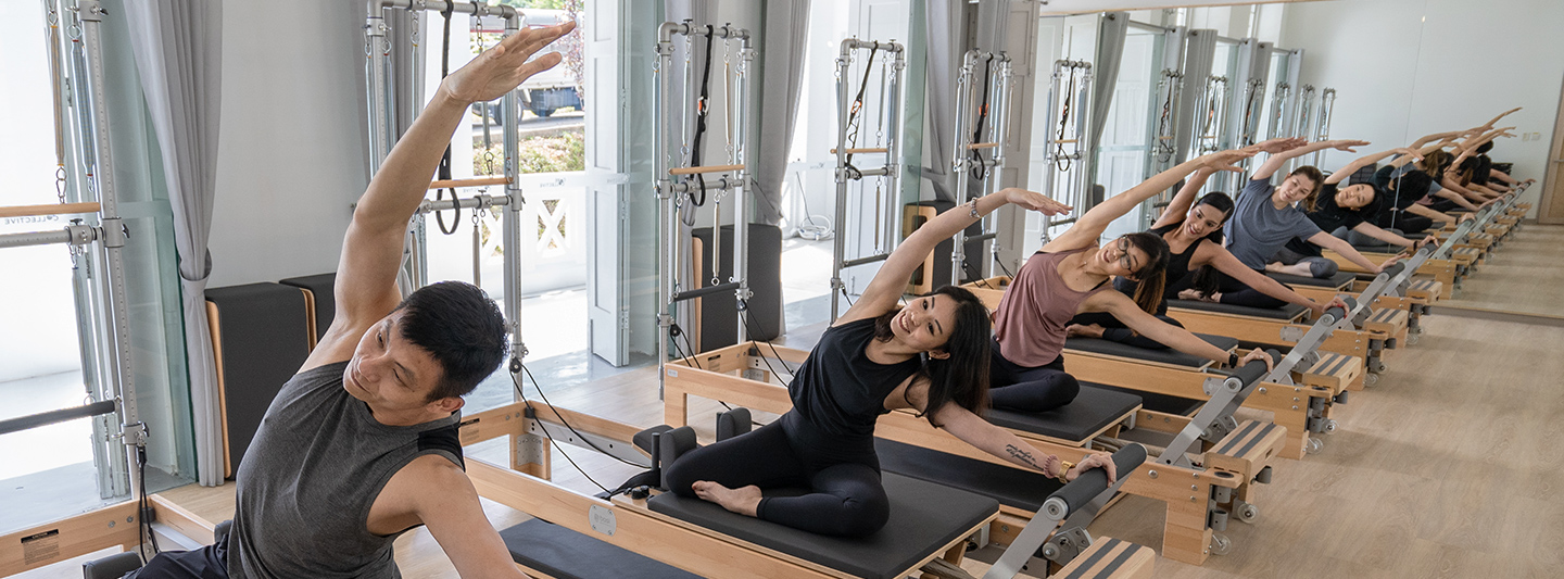 people doing pilates on a reformer