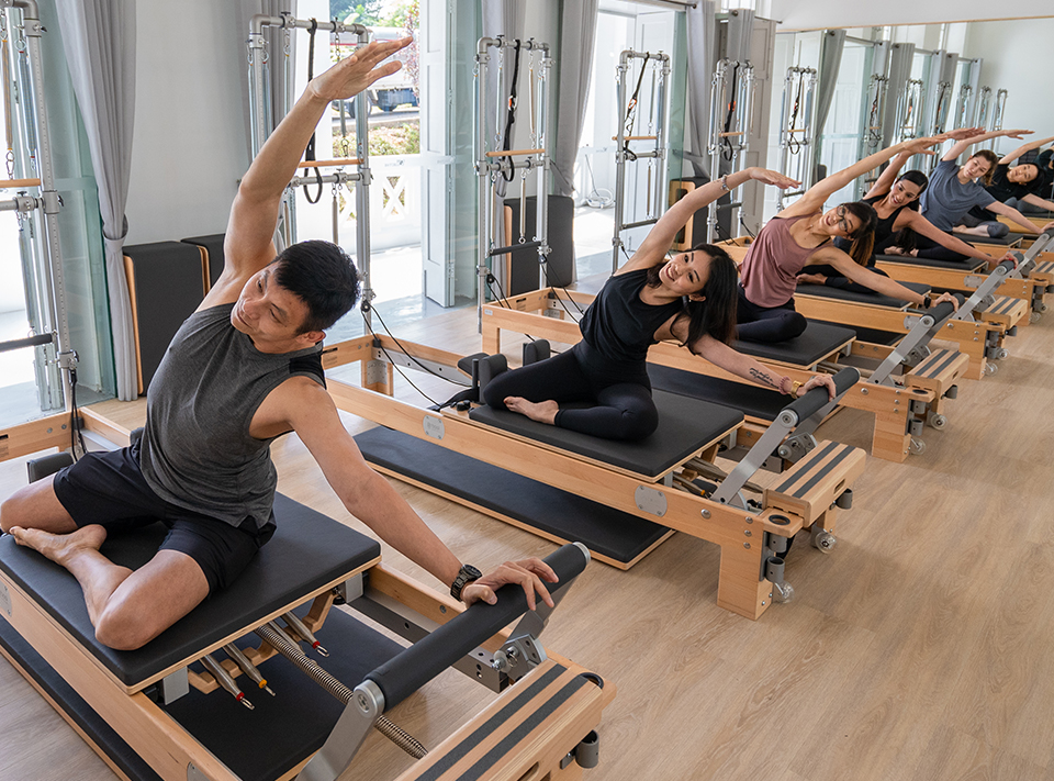 people doing pilates exercises on reformers