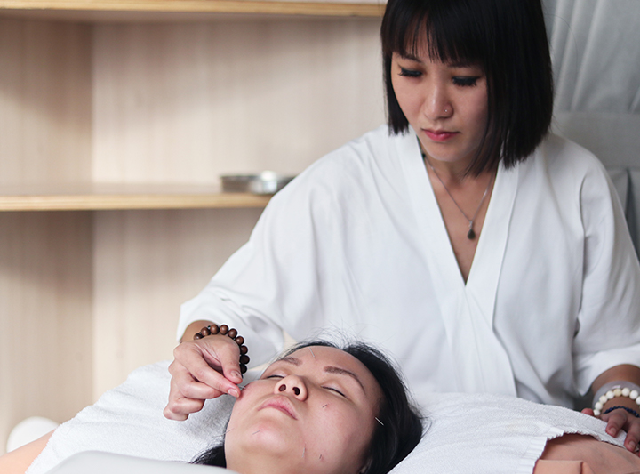 traditional chinese medicine doctor performing acupuncture on patient