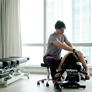chiropractor adjusting client spine