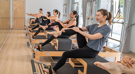 Group of people doing pilates reformer
