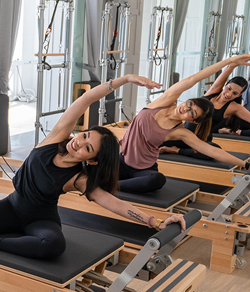 adults doing pilates exercises on reformers