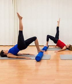 People doing mat exercises with foam roller