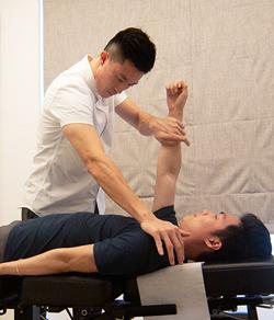 chiropractor adjusting client's spine