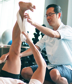 physiotherapist stretching client's leg